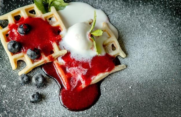 Frisch gebackene hausgemachte klassische belgische waffeln mit eiscreme, frischen blaubeeren und minze, ansicht von oben nach unten. herzhafte waffeln. frühstückskonzept.