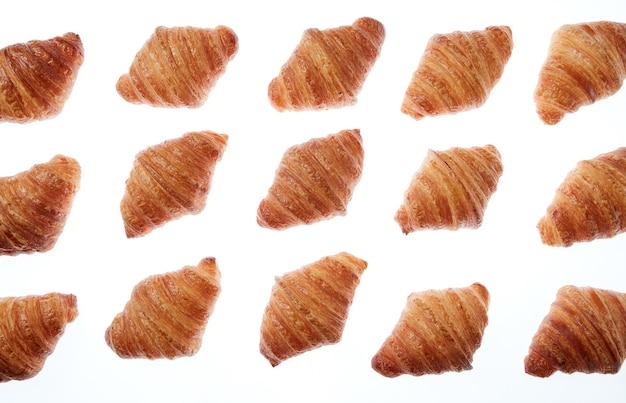 Frisch gebackene hausgemachte köstliche croissants muster auf einem weißen hintergrund. kontinentales frühstückskonzept.