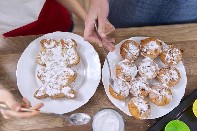 Frisch gebackene hausgemachte muffins auf dem tisch mit zuckerblase bestreut. amerikanische muffins und cupcake in katzenform