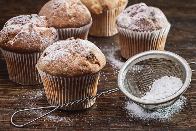 Frisch gebackene hausgemachte muffins mit puderzucker auf holzoberfläche. puderzucker im sieb.