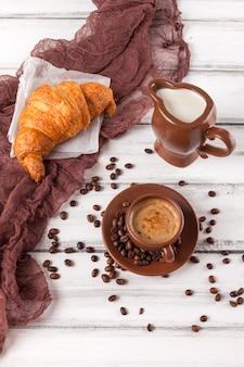 Frisch gebackene hörnchen auf brauner serviette, creme, zu tasse kaffees in den keramischen tellern auf weißem hölzernem hintergrund. frisches gebäck zum frühstück. leckeres dessert. nahaufnahmefotografie. vertikale banner.