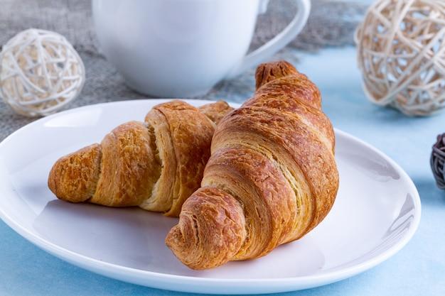 Frisch gebackene hörnchen auf einer platte und einer schale heißem tee zum französisches frühstück