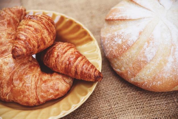 Frisch gebackene hörnchen, bäckereibrot auf sack im selbst gemachten frühstücksnahrungskonzept der tabelle