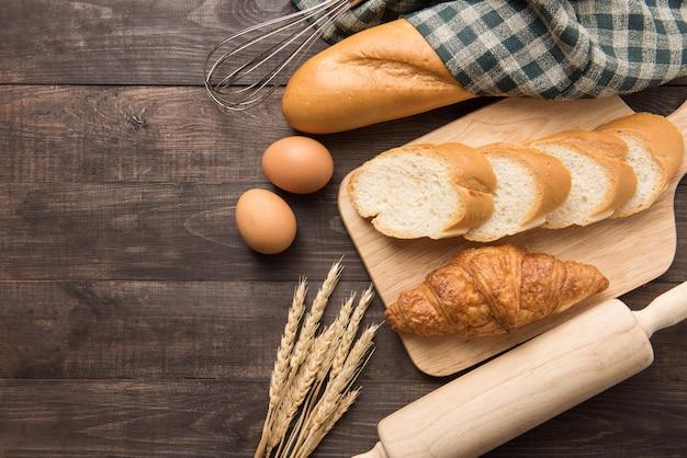 Frisch gebackene hörnchen, stangenbrot und eier auf hölzernem hintergrund