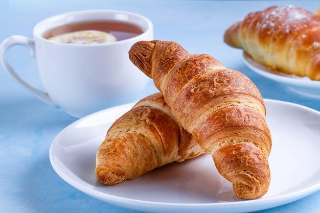 Frisch gebackene hörnchen und eine schale heißer tee mit zitrone zum französisches frühstück auf einem blauen hintergrund