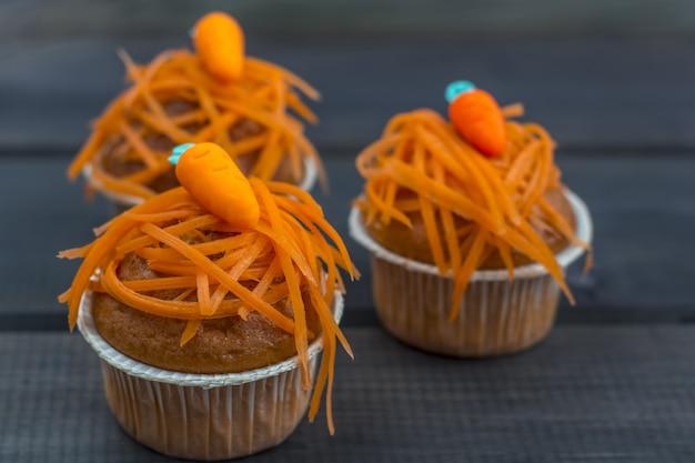 Frisch gebackene karottenmuffins, verziert mit frischen karottenchips und marzipan-karotten auf hölzernem hintergrund. nationaler karottenkuchentag.