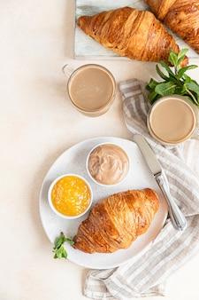 Frisch gebackene knusprige französische croissants mit marmelade, schokoladencreme und kaffee