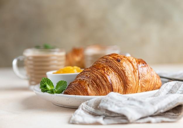 Frisch gebackene knusprige französische croissants mit marmelade und schokoladencreme und zwei kaffeetassen frühstück