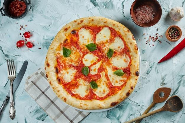 Frisch gebackene knusprige pizza mit tomaten und mozzarella. pizza margherita auf einem grauen tisch in einer komposition mit zutaten und küchenutensilien
