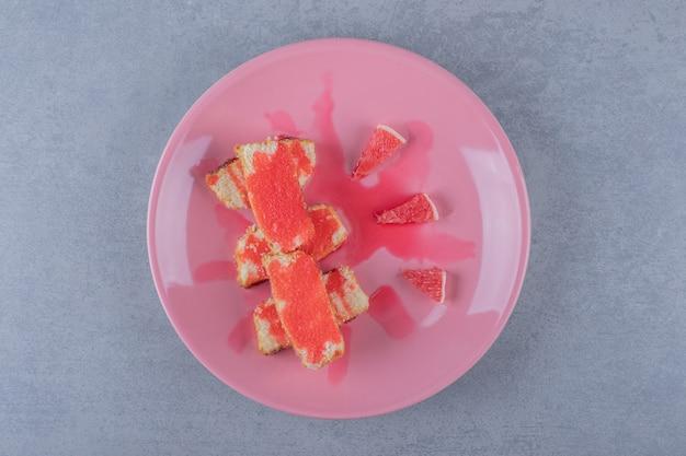 Frisch gebackene kuchenstücke mit grapefruitscheiben