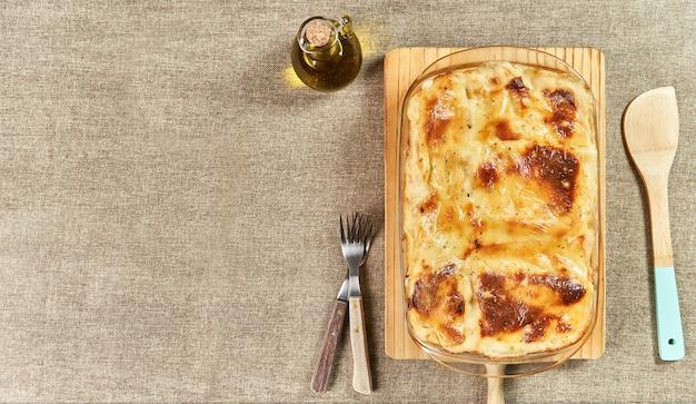 Frisch gebackene lasagne mit geschmolzenem käse, serviert mit einem holzspatel
