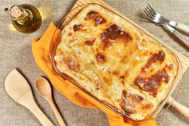 Frisch gebackene lasagne mit geschmolzenem käse und gratin auf rustikalem tisch