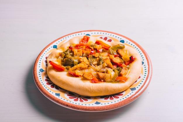 Frisch gebackene mini-pizza mit hühnchen und zwiebeln. traditionelles spanisches gebäck mit gemüse.