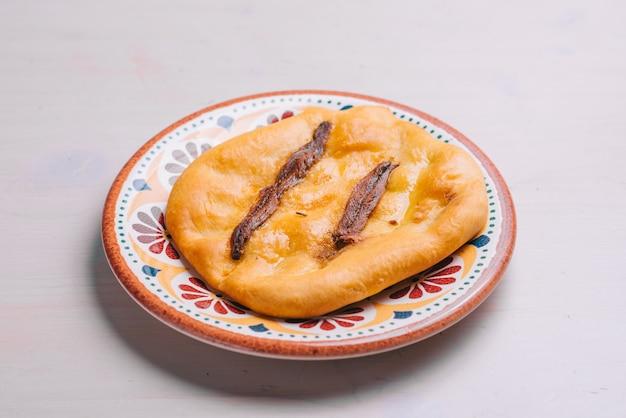 Frisch gebackene minipizza mit sardellen und öl. traditionelles spanisches gebäck mit gemüse.