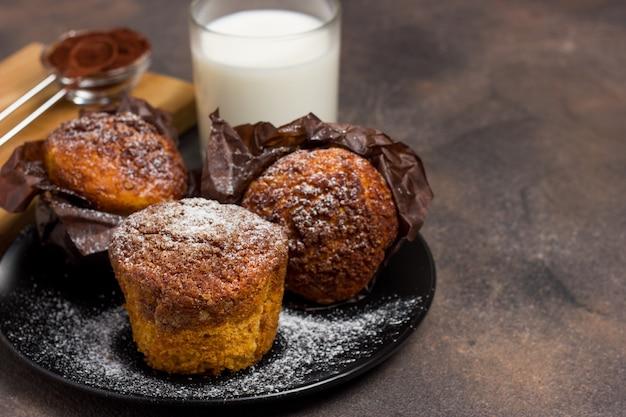 Frisch gebackene muffins mit kakao, zimt und haferkrümel auf einem natürlichen holzbrett