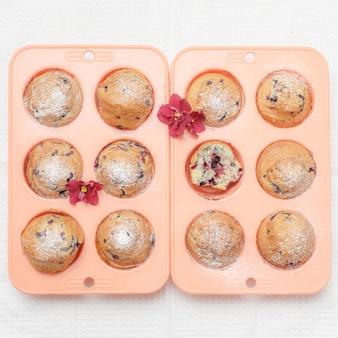 Frisch gebackene muffins oder cupcakes in rosa silikonbackformen, draufsicht