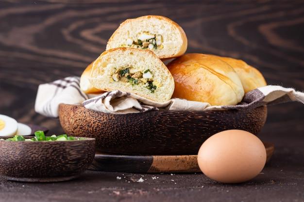 Frisch gebackene pastetchen mit ei und frühlingszwiebelfüllung. traditionelle russische und ukrainische pikante pirozhki.