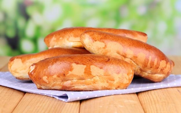 Frisch gebackene pasteten, auf holztisch, auf hellem