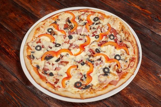 Frisch gebackene pizza auf holzwand