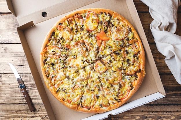 Frisch gebackene pizza in einer pappschachtel auf einem holztisch.