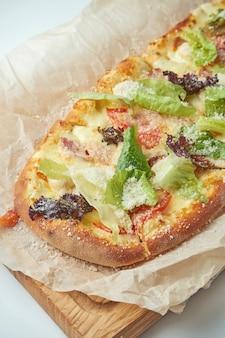 Frisch gebackene pizza margherita mit eisbergsalat, parmesan, crackern und hühnchen auf einem holztablett auf einem grauen tisch. italienische küche
