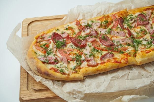 Frisch gebackene pizza margherita mit geräucherten würstchen, speck, roter sauce und mozzarella auf einem holztablett auf einem grauen tisch. italienische küche