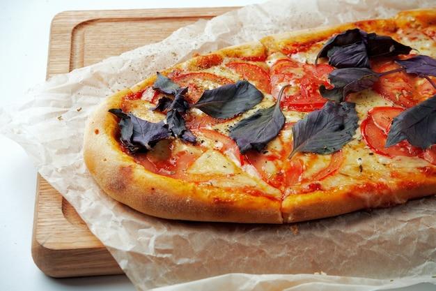Frisch gebackene pizza margherita mit tomaten, käse und basilikum auf einem holztablett auf einem grauen tisch. italienische küche
