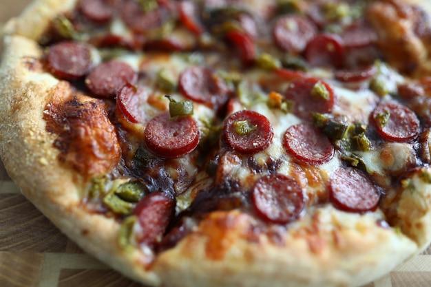 Frisch gebackene pizza mit knusprigem käse und heißen, leckeren peperoni, essfertig aus der nähe