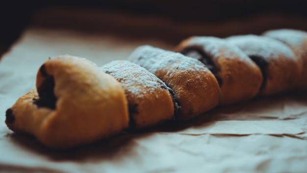 Frisch gebackene schokobrötchen mit leckerer füllung, bestreut mit puderzucker. vor dem hintergrund von braunem kraftpapier