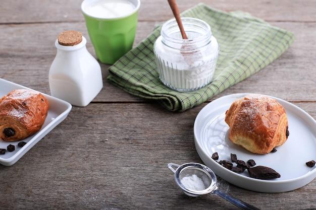 Frisch gebackene schokoladencroissants (pain au chocolat) mit milch zum frühstück. serviert auf weißer platte auf rustikalem tisch kopienraum für text