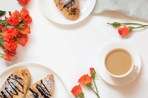 Frisch gebackene schokoladenhörnchen und -tasse kaffee auf weiß. ansicht von oben. weibliches frühlingsfrühstückskonzept. kopieren sie platz.