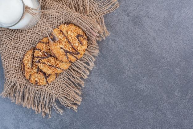 Frisch gebackene sesamkekse und milch auf sackleinen.