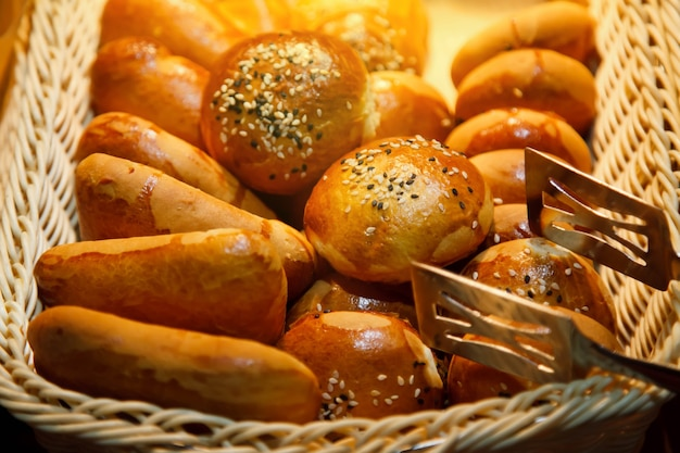 Frisch gebackene süße blätterteigbrötchen mit schokolade und kokoskrumen im hölzernen weidenkorb sind essfertig. konzept des frühstücks oder brunchs. hintergrund für website oder banner. platz kopieren