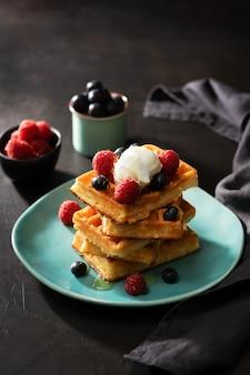 Frisch gebackene waffeln mit himbeeren, beeren, honig und kaffee zum frühstück oder brunch