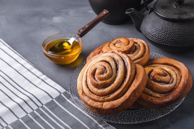 Frisch gebackene zimtschnecken mit honig.