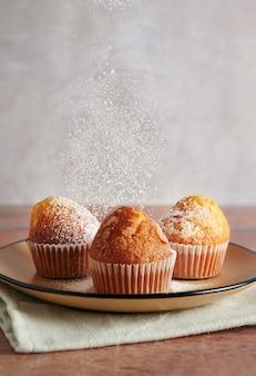 Frisch gebackenen muffins und hausgemachten kuchen mit puderzucker bestreuen.