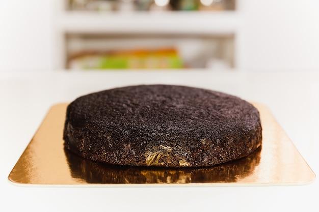 Frisch gebackener biskuitkuchen mit auf goldenem karton