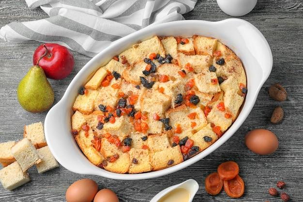 Frisch gebackener brotpudding in auflaufform und zutaten auf holztisch