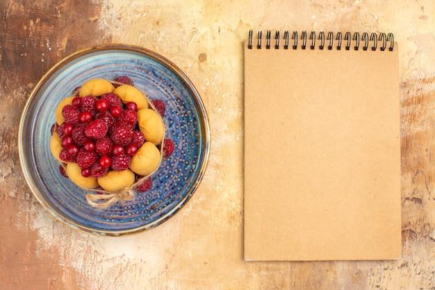 Frisch gebackener geschenkkuchen mit früchten und notizbuch auf mischfarbtabelle