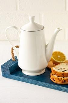 Frisch gebackener hausgemachter rosinenlaibkuchen auf holztablett mit teekanne. frühstück.