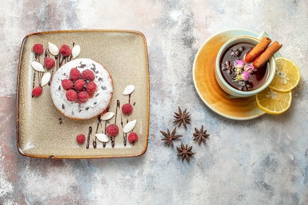 Frisch gebackener kuchen mit himbeeren eine tasse schwarzen tee mit zitrone und zimtlimette