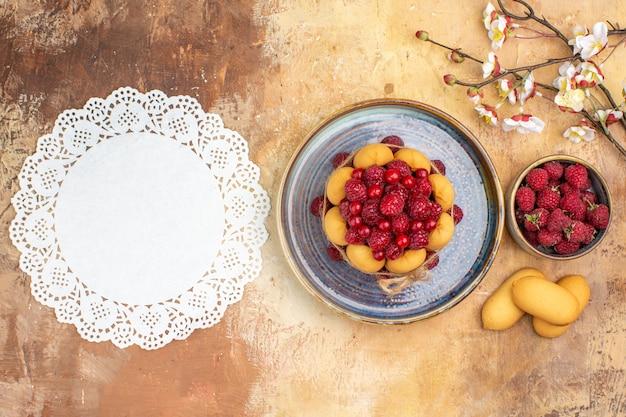 Frisch gebackener weicher kuchen mit fruchtkeksen und serviette auf gemischtem farbtisch