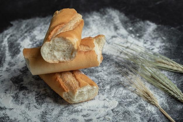 Frisch gebackenes baguette mit gerste auf weißem hintergrund.