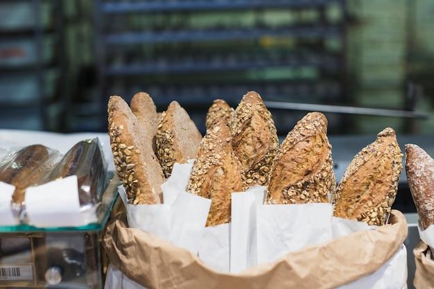 Frisch gebackenes baguettebrot im papier mit verschiedenen samen