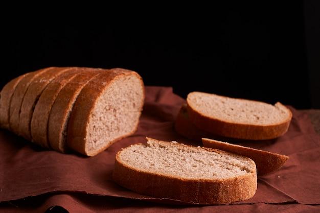 Frisch gebackenes brot auf dunklem hölzernem küchentisch. tiefenschärfe