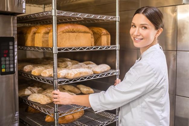 Frisch gebackenes brot. hübsche frau, die ihr gesicht zur kamera dreht, die nahe ofen und tabletts des brotes in der guten stimmung steht