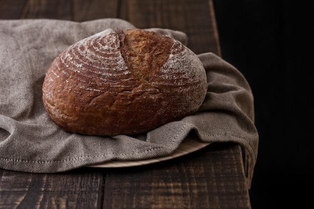 Frisch gebackenes brot mit geschirrtuch auf dunklem hölzernem brett