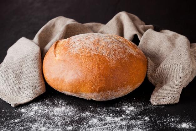 Frisch gebackenes brot mit mehl und geschirrtuch auf schwarzem hintergrund