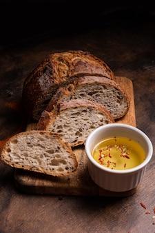 Frisch gebackenes brot mit olivenöl auf einem holzbrett