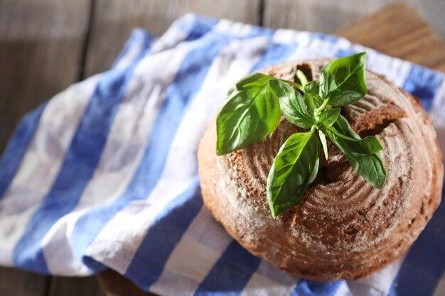 Frisch gebackenes brot und frisches basilikum auf küchentuch, auf holztisch